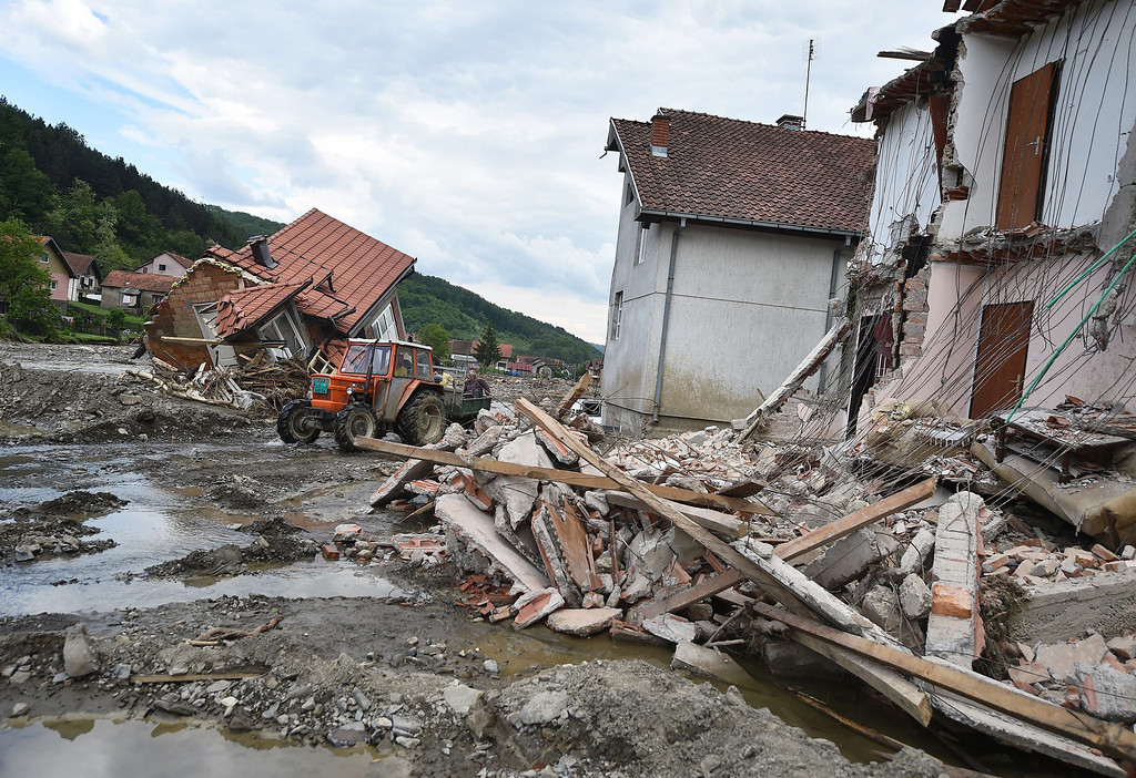 Description of . People ride a tractor among houses damaged by flooding and landslides in Krupanj, some 130 kilometers south west of Belgrade, on May 20, 2014, after the western Serbian town was hit with floods and landslides, cutting it off for four days. Serbia declared three days of national mourning on May 20 as the death toll from the worst flood to hit the Balkans in living memory rose and health officials warned of a possible epidemic.  AFP PHOTO / ANDREJ  ISAKOVIC/AFP/Getty Images