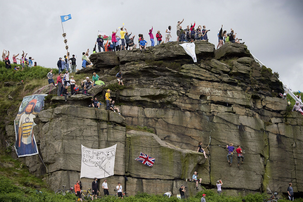 Description of . Supporters are pictured on a rock near the road during the 201 km second stage of the 101th edition of the Tour de France cycling race on July 6, 2014 between York and Sheffield, northern England.  AFP PHOTO / JEFF PACHOUDJEFF PACHOUD/AFP/Getty Images