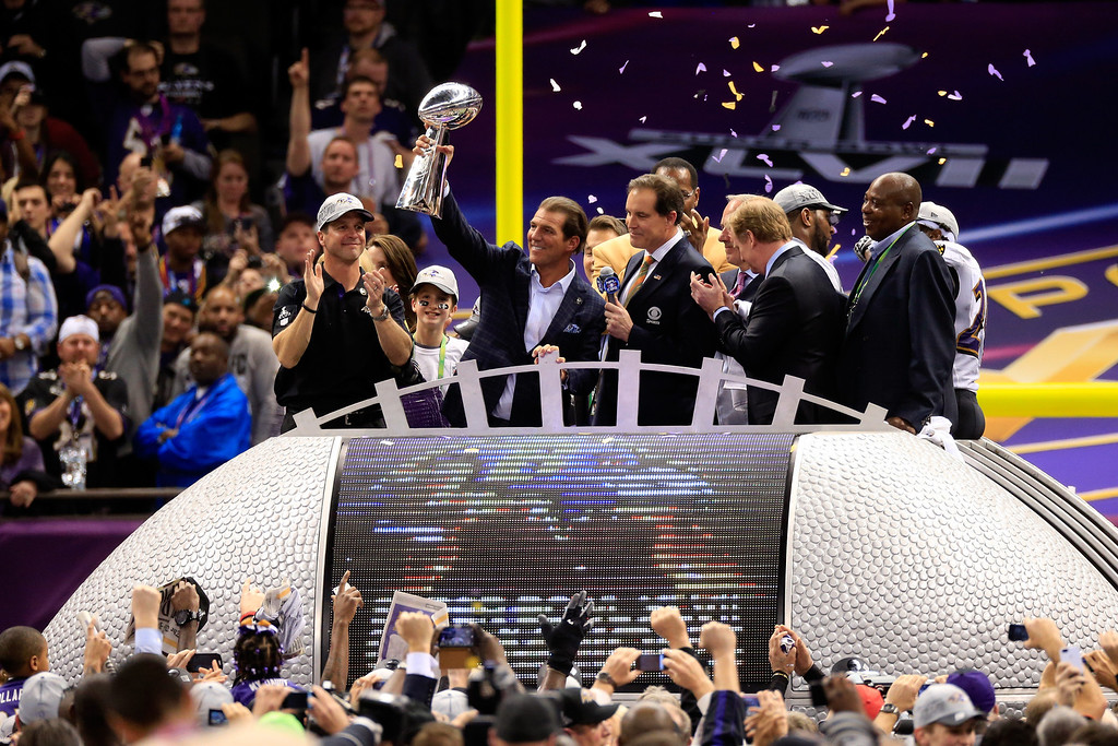 Description of . Baltimore Ravens owner Steve Bisciotti holds up the Vince Lombardi Trophy in front of head coach John Harbaugh and CBS host Jim Nantz during Super Bowl XLVII at the Mercedes-Benz Superdome on February 3, 2013 in New Orleans, Louisiana.  (Photo by Jamie Squire/Getty Images)