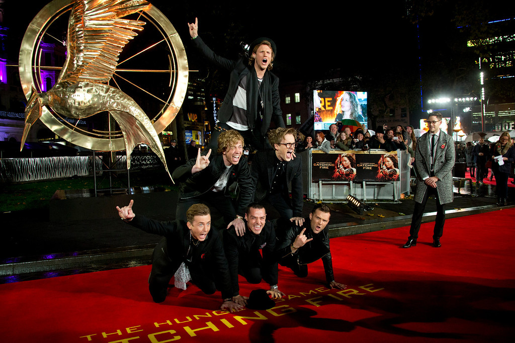 Description of . British boybands McFly and Busted, who have teamed up to form the group McBusted, form a human pyramid on the red carpet for the World Premiere of Hunger Games: Catching Fire, at a central London cinema, Monday, Nov. 11, 2013. (Photo by Joel Ryan/Invision/AP)