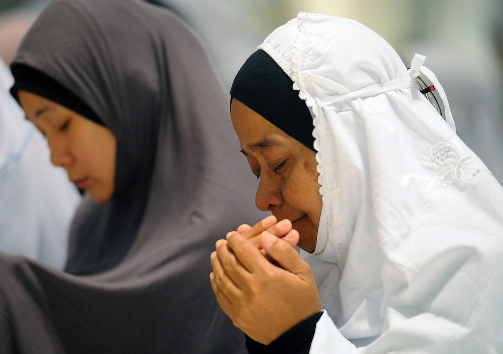 Description of . A Malaysian Muslim woman cries as she offers a special prayer for passengers aboard a missing plane, at a mosque in Putrajaya, Malaysia, Sunday, March 9, 2014. Military radar indicates that the missing Boeing 777 jet may have turned back before vanishing, Malaysia's air force chief said Sunday as authorities were investigating up to four passengers with suspicious identifications. (AP Photo/Joshua Paul)