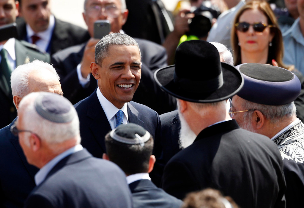 Description of . U.S. President Barack Obama (C) speaks to Israel's Chief Rabbis Shlomo Amar (R) and Yona Metzger (2nd R) during an official welcoming ceremony at Ben Gurion International Airport near Tel Aviv March 20, 2013. REUTERS/Darren Whiteside