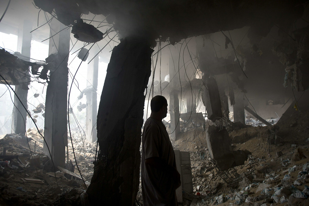 Description of . A Palestinian man inspects the rubble of a destroyed store located on the ground floor of a building hit by an Israeli air strike on July 22, 2014 in Gaza city. UN chief Ban Ki-moon and US Secretary of State John Kerry are in Cairo today in a bid to broker a truce between Israel and Hamas after two weeks of fighting which has left over 570 Palestinians dead. AFP PHOTO / MAHMUD HAMS/AFP/Getty Images