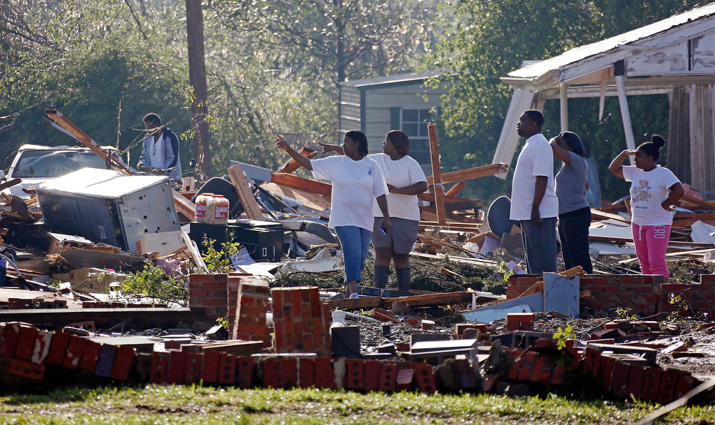 Description of . Friends and relatives search through the remains of a child care center in Louisville, Miss., Tuesday, April 29, 2014. The facility and the auto repair shop next door were demolished by a tornado Monday. (AP Photo/Rogelio V. Solis)