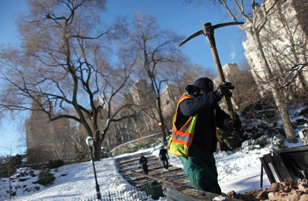 Description of . Carlos Guzman, gardener with the New York City Department of Parks & Recreation, breaks up salt to be used on snow in Carl Schurz Park after an overnight storm dropped up to 7 inches of snow on January 04, 2014 in New York City. The Northeast and Midwest regions of the United States were hit with a large amount of snowfall accompanied by blizzard-like winds and plummeting temperatures this week. (Photo by Yana Paskova/Getty Images)