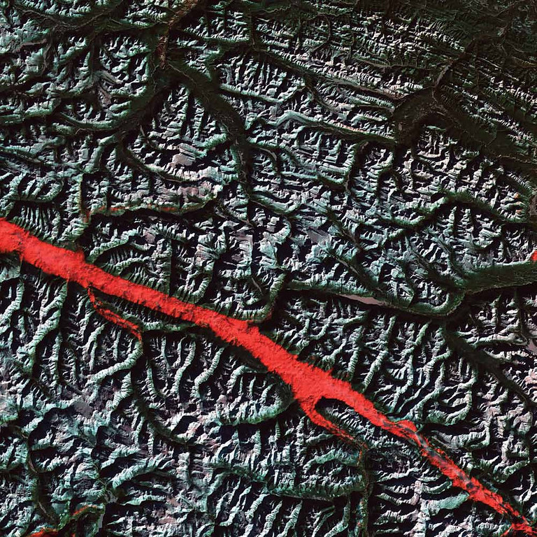 Description of . Rocky Mountain Trench, Canada The stroke of red in this 2004 Landsat 5 image is a remarkable interplay of light and cloud in the Canadian Rockies. The Rocky Mountain Trench is a valley that stretches from the U.S. state of Montana to just south of Canada�s Yukon Territory. It runs parallel with the peaks of the Canadian Rockies, ranging from 3 to 16 kilometers wide. Low clouds filled a part of the Trench near the border between the Canadian provinces of Alberta and British Columbia. The light-reflecting nature of the clouds coupled with low Sun elevation resulted in this startling effect. The Trench aligns with the Fraser River and makes its way past Mount Robson, the highest peak in the Canadian Rockies. Mount Robson is near the center of this image.   NASA