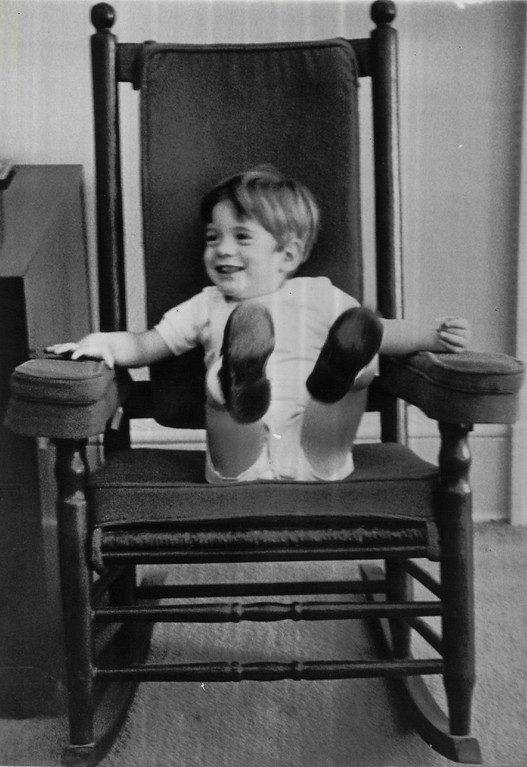 Description of . Three-year-old John F. Kennedy, Jr., kicks back and forth in a rocking chair, something his father was instrumental in re-popularizing, in the White House office of the president's secretary, Mrs. Evelyn Lincoln, in 1963.  Denver Post file