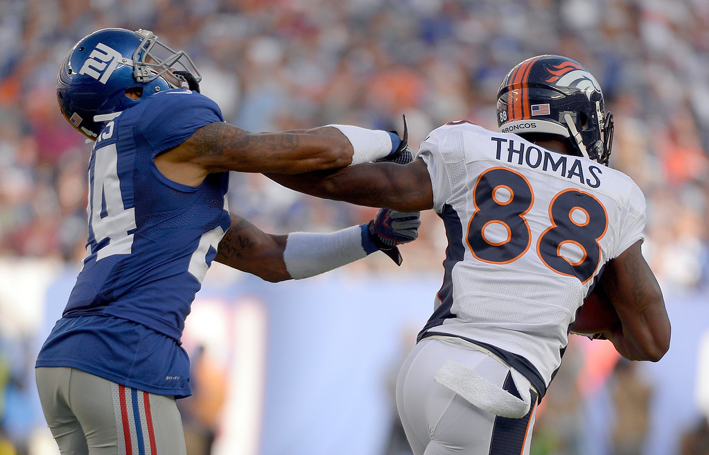 Description of . Denver Broncos wide receiver Demaryius Thomas (88) stiff arms New York Giants defensive back Terrell Thomas (24) as he picks up a few yards during the second quarter September 15, 2013 MetLife Stadium. (Photo by John Leyba/The Denver Post)