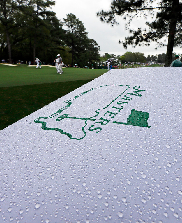 Description of . Golfers walk past an umbrella during a light rain storm during the second round of the Masters golf tournament Friday, April 12, 2013, in Augusta, Ga. (AP Photo/David J. Phillip)