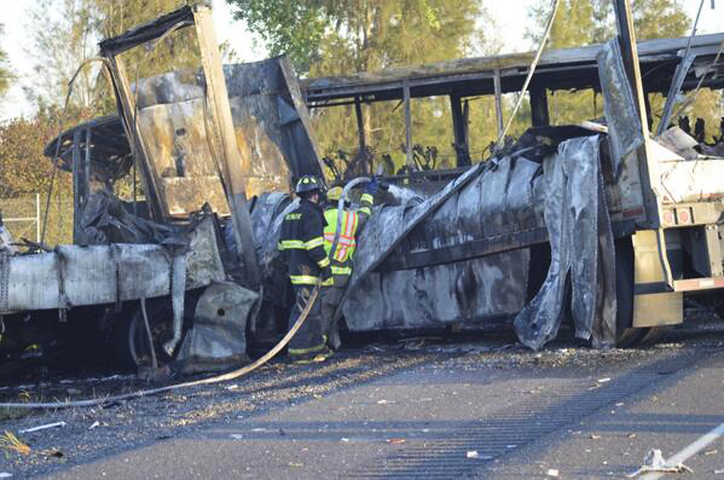 Description of . Firefighters hose down the wreckage of a bus and a semitruck that collided, Thursday, April 10, 2014, just north of Orland, Calif., that left at least nine dead. Authorities said it is not yet clear what caused the crash but that it involved a tour bus, a FedEx truck and a Nissan Altima. (AP Photo/The Chico Enterprise-Record, Dan Reidel)