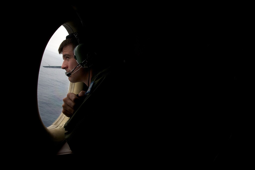Description of . A crewman of an RAAF AP-3C Orion aircraft looks out his observation window whilst searching for the missing Malaysia Airways Flight MH370 over the Indian Ocean on March 24, 2014. Australian Prime Minister Tony Abbott told Parliament on March 24 that a Royal Australian Air Force P-3 Orion aircraft had located two new objects floating in the southern Indian Ocean.  AFP PHOTO/POOL/RICHARD  WAINWRIGHT/AFP/Getty Images