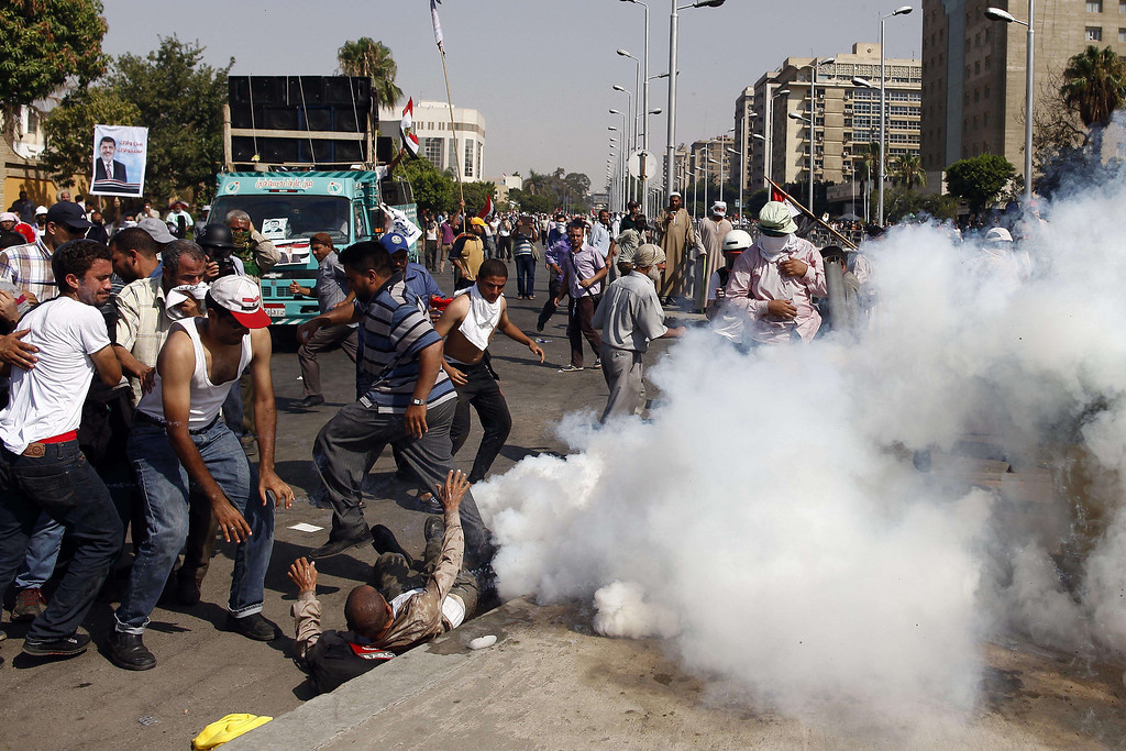 Description of . Supporters of ousted Egyptian president Mohamed Morsi take cover from tear gas during clashes outside the headquarters of the Republican Guard in Cairo on July 5, 2013. At least three supporters of Morsi were killed and many others were wounded as they gathered for a protest, an AFP correspondent said. Shooting could be heard coming from both the Republican Guard and the ranks of the protesters. MAHMOUD KHALED/AFP/Getty Images