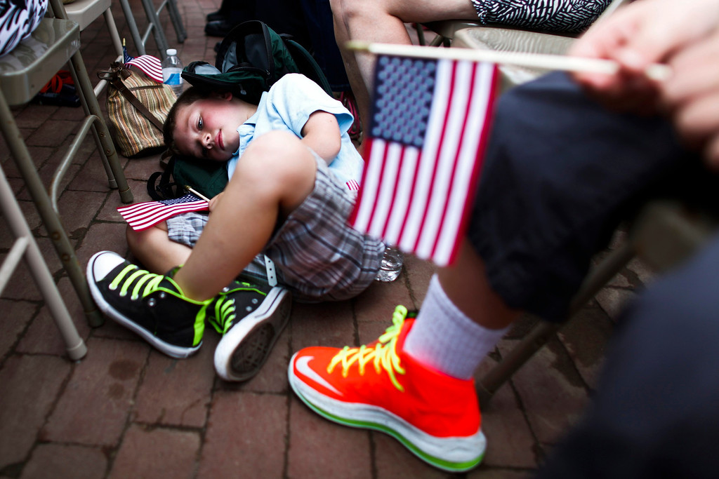 Description of . A child rests during a ceremony at the Statue of Liberty and Liberty Island during its reopening to the public in New York July 4, 2013. Under steamy summer skies, tourists in New York flocked to ferries headed for the Statue of Liberty, re-opening with an Independence Day ceremony after closing in October as Superstorm Sandy approached.  REUTERS/Eduardo Munoz