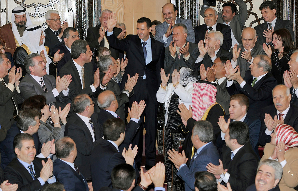 Description of . FILE - In this photo provided by the Syrian official news agency SANA, Syrian President Bashar Assad, center top, greets lawmakers before his speech at the Parliament in Damascus, Syria, Wednesday, March 30, 2011. (AP Photo/SANA, File)
