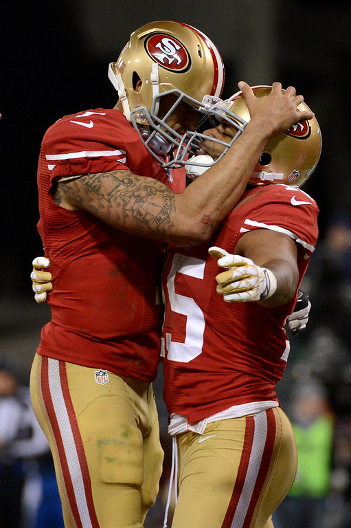 Description of . Wide receiver Michael Crabtree #15 of the San Francisco 49ers hugs quarterback Colin Kaepernick #7 after a touchdown in the second quarter against the Green Bay Packers during the NFC Divisional Playoff Game at Candlestick Park on January 12, 2013 in San Francisco, California.  (Photo by Harry How/Getty Images)