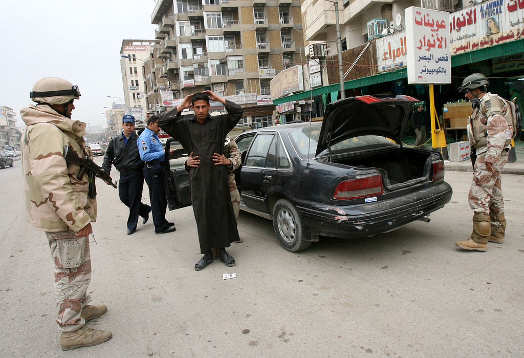 Description of . Iraqi army soldiers search a driver at a vehicle checkpoint in central Baghdad, Iraq, Saturday, Feb. 10, 2007. Although Iraqis have seen an increase in the number of checkpoints and other security measures, there is little sign of a