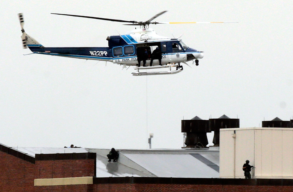 Description of . A Park Police helicopter hovers above snipers on the roof of a building at the Navy Yard complex where a shooting took place early this morning September 16, 2013 in Washington, DC. Early reports indicate that several people may have been shot, and police are still trying to determine the number of suspects involved in the shooting. (Photo by Win McNamee/Getty Images)