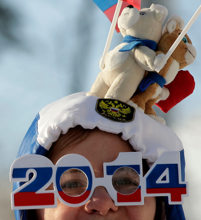 Description of . A fan watches during the men\'s cross-country sprint at the 2014 Winter Olympics, Tuesday, Feb. 11, 2014, in Krasnaya Polyana, Russia. (AP Photo/Charlie Riedel)