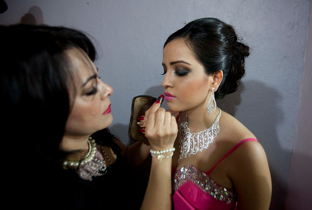 Description of . In this Jan. 26, 2013 photo, Magdabelyn Parra Gamez, who goes by Belyn, holds still as her lipstick is applied backstage as she competes in the