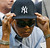 Muhammad Ali adjusts a New York Yankees cap given to him by Yankees shortstop Derek Jeter before the Red Sox faced the Yankees in a baseball game at Yankee Stadium in New York, Thursday, Aug. 6, 2009. (AP Photo/Kathy Willens)