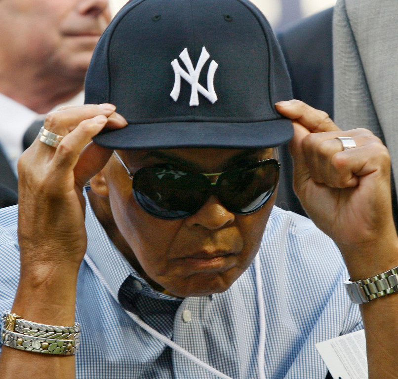 Description of . Muhammad Ali adjusts a New York Yankees cap given to him by Yankees shortstop Derek Jeter before the Red Sox faced the Yankees in a baseball game at Yankee Stadium in New York, Thursday, Aug. 6, 2009. (AP Photo/Kathy Willens)