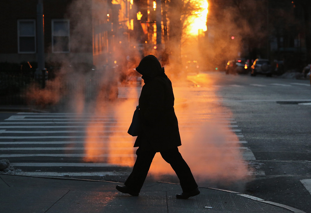 Description of . A pedestrian braves the cold on January 7, 2014 in New York City. A 'polar vortex'  of frigid air centered on the North Pole dropped temperatures to a record low 4 degrees in New York City. (Photo by John Moore/Getty Images)