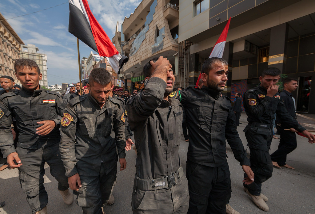 Description of . Members of the Iraqi security forces mourn during the funeral procession of their comrades in Iraq's Shiite shrine city of Karbala on October 27, 2014 after a suicide bomber detonated an explosives-rigged Humvee armoured vehicle near security forces and allied militiamen in Jurf al-Sakhr, south of Baghdad, killing over a dozen. Security forces and militia allies have fought for months to regain ground in Jurf al-Sakhr from Islamic State (IS) group fighters, which spearheaded a major militant offensive that has overrun large areas since June. MOHAMMED SAWAF/AFP/Getty Images