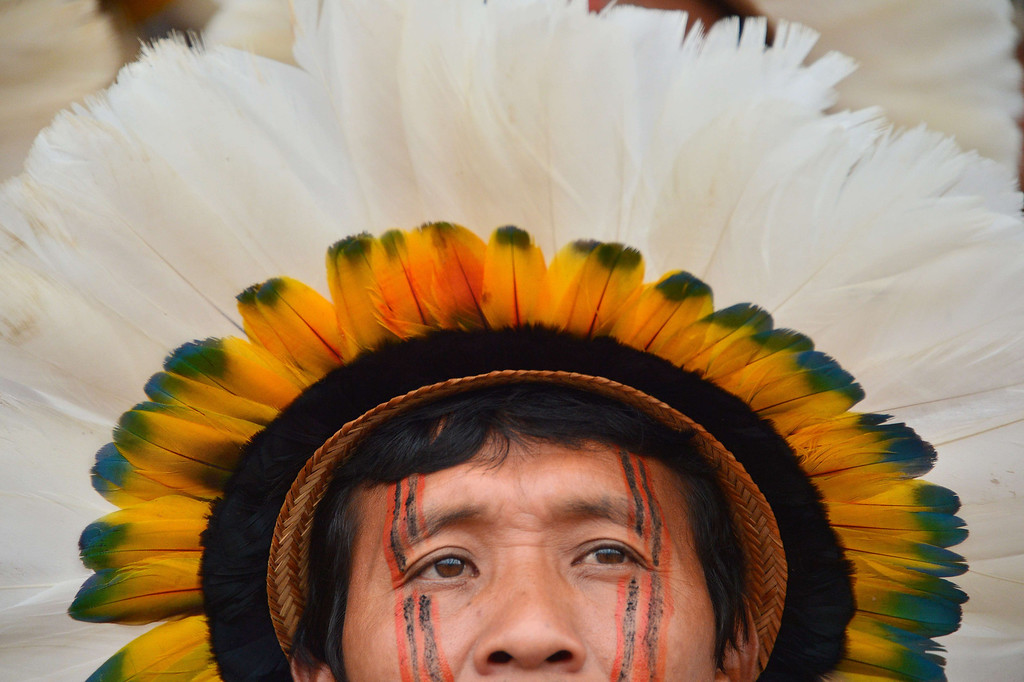 Description of . A Brazilian indigenous man of the Rikbaktsa tribe watches the bow and arrow competition during the XII International Games of Indigenous Peoples in Cuiaba, Mato Grosso state, Brazil on November 12, 2013.  AFP PHOTO / Christophe  SIMON/AFP/Getty Images