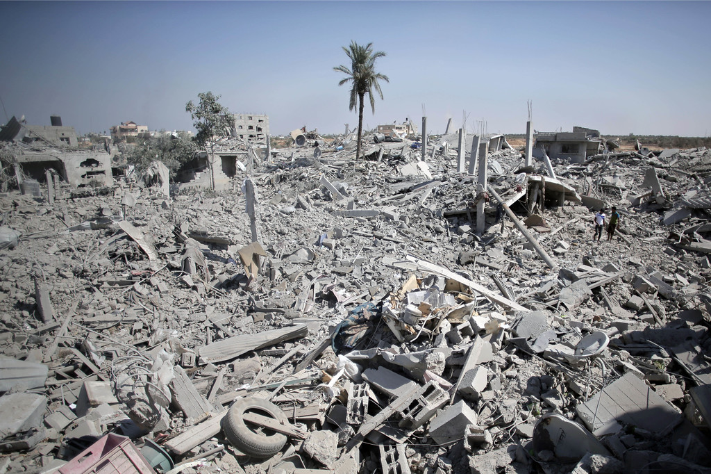 Description of . Palestinians inspect the damage of their destroyed houses following Israeli strikes in the village of Khuzaa, southern Gaza Strip, close to the Israeli border, Friday, Aug. 1, 2014. A three-day Gaza cease-fire that began Friday quickly unraveled, with Israel and Hamas accusing each other of violating the truce. (AP Photo/Khalil Hamra)