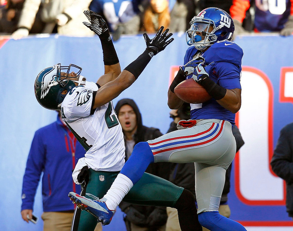 Description of . New York Giants Rueben Randle (R) catches a pass he took in for a touchdown next to Philadelphia Eagles Nnamdi Asomugha (L) in the first quarter during their NFL football game in East Rutherford, New Jersey, December 30, 2012. REUTERS/Gary Hershorn
