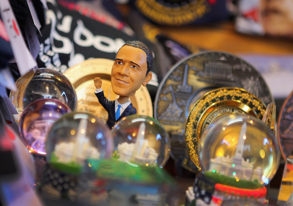 Description of . A U.S. President Barack Obama doll is displayed in a souvenir shop as preparations continue for the Presidential Inauguration on January 20, 2013 in Washington, DC.  The U.S. capital is preparing for the second inauguration of U.S. President Barack Obama, which will take place on January 21.  (Photo by Joe Raedle/Getty Images)