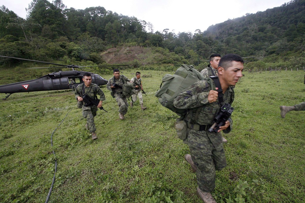 Description of . Soldiers disembark from a helicopter at La Pintada, state of Guerrero, Mexico, on September 19, 2013 as heavy rains hit the country.  AFP PHOTO/Pedro PARDO/AFP/Getty Images