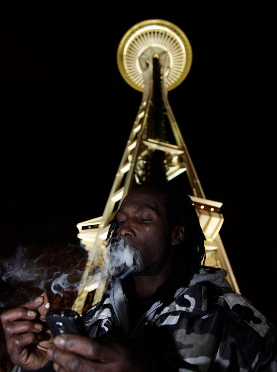 Description of . Allister Adams smokes marijuana, Thursday, Dec. 6, 2012, just after midnight at the Space Needle in Seattle. Possession of marijuana became legal in Washington state at midnight, and several hundred people gathered at the Space Needle to smoke and celebrate the occasion, even though the new law does prohibit public use of marijuana. (AP Photo/Ted S. Warren)