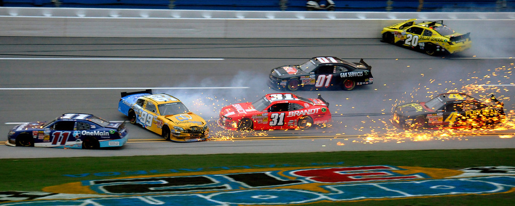 Description of . Elliott Sadler (11), Mike Wallace (01), Justin Allgaier (31), Alex Bowman (99), Brian Vickers (20) and Landon Cassill (4) spin through the tri-oval near the end of the NASCAR Nationwide Series auto race at the Talladega Superspeedway in Talladega, Ala., Saturday, May 4, 2013.  (AP Photo/Dan Lighton)