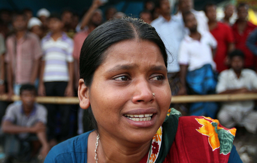 Description of . A woman cries for her missing husband, believed to be trapped in the rubble of a building that collapsed, in Savar, near Dhaka, Bangladesh, Wednesday, May 1, 2013. Emergency workers hauling large concrete slabs from a collapsed 8-story building said Tuesday they expect to find many dead bodies when they reach the ground floor, indicating the death toll will be far more than the official 386. One estimate said it could be as high as 1,400. The illegally constructed, 8-story Rana Plaza collapsed on the morning of April 24, bringing down the five garment factories inside. (AP Photo/Palash Khan)