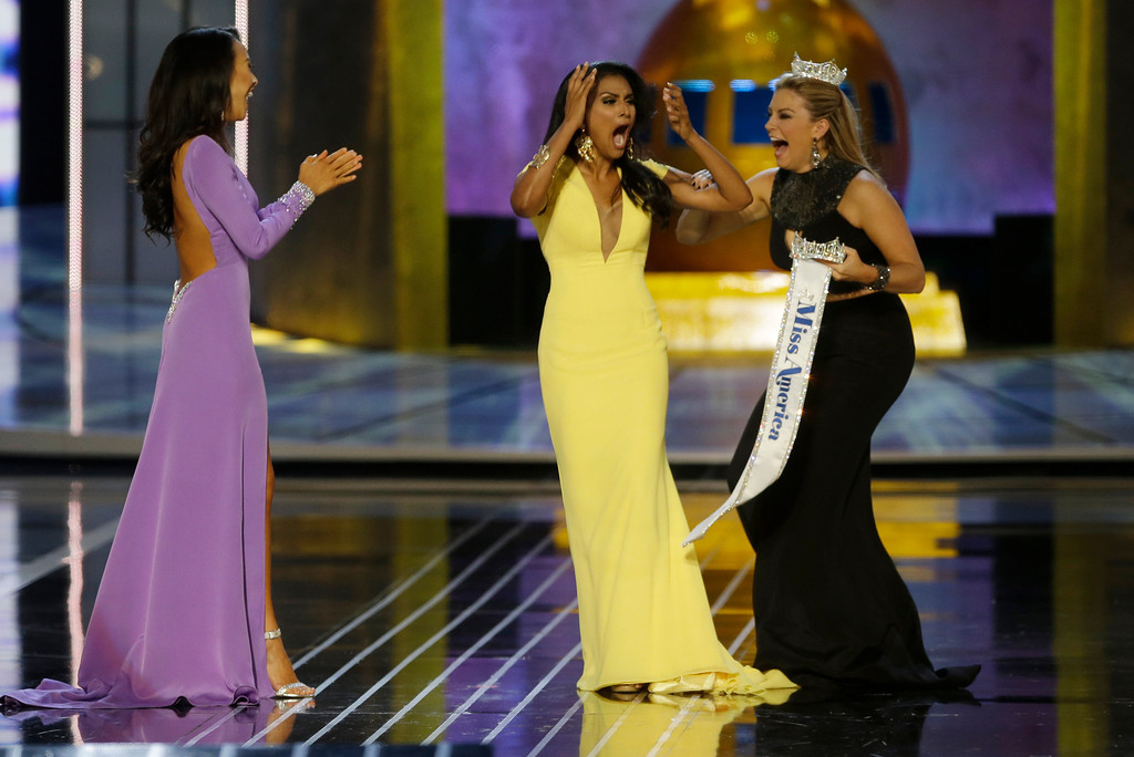 Description of . Miss New York Nina Davuluri, center, reacts after being named Miss America 2014 pageant as Miss California Crystal Lee, left, and Miss America 2013 Mallory Hagan celebrate with her, Sunday, Sept. 15, 2013, in Atlantic City, N.J. (AP Photo/Mel Evans)