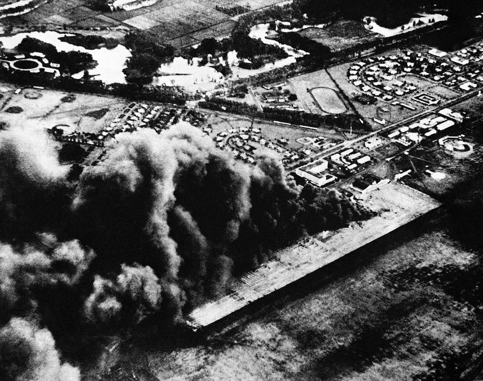 Description of . Flaming oil throws a billow of smoke skyward in the Japanese attack on Hickam Field, Pearl Harbor, U.S. Air base near Honolulu, Dec. 7, 1941. (AP Photo)