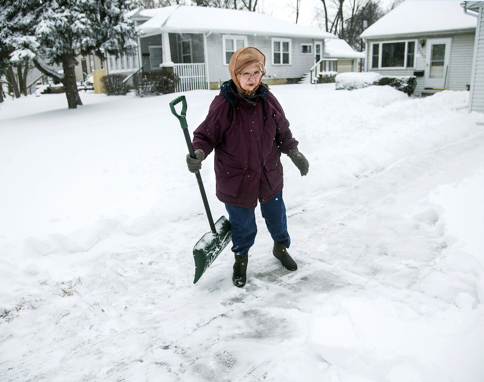 Description of . Violet Malkowski, 81, stands in her driveway in Champaign, Ill., on Wednesday, Feb. 5, 2014. Malkowski said this was her third try at clearing the driveway this morning. (AP Photo/The News-Gazette, John Dixon)