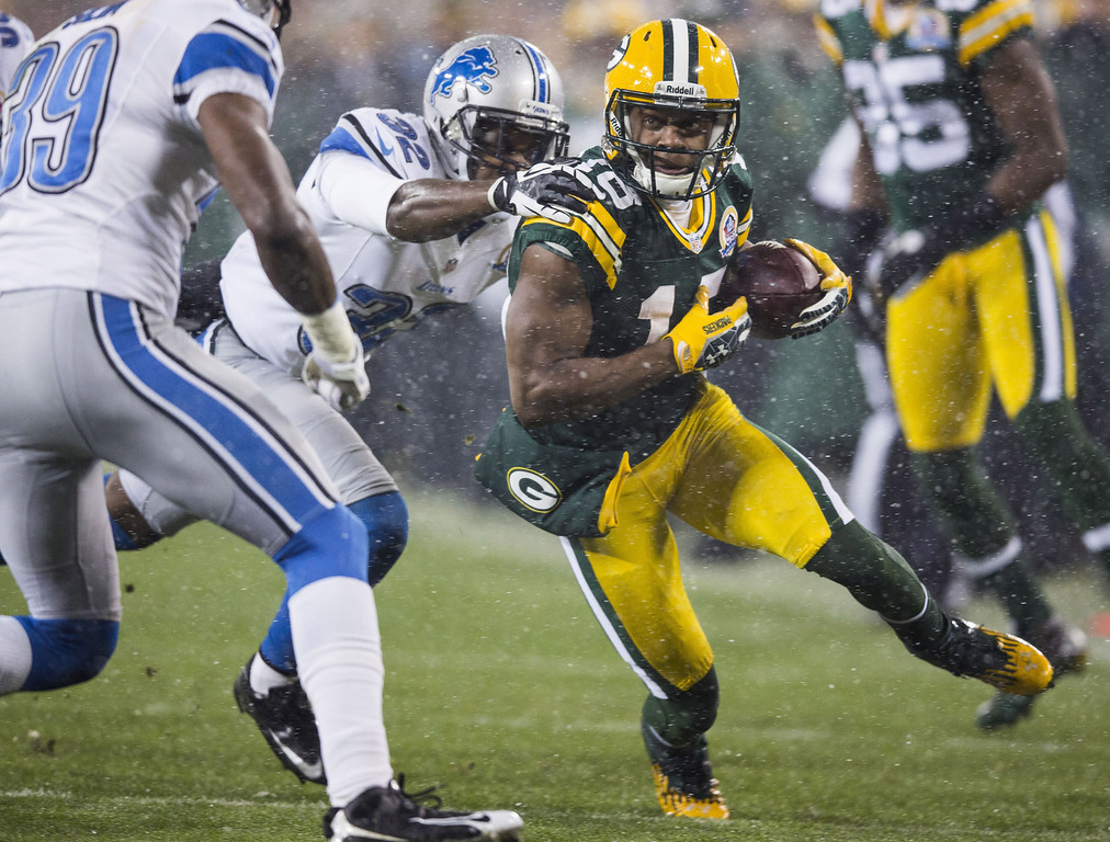 Description of . GREEN BAY, WI - DECEMBER 9:  Randall Cobb #18 of the Green Bay Packers breaks through a tackle by Don Carey #32 of the Detroit Lions at Lambeau Field on December 9, 2012 in Green Bay, Wisconsin.  (Photo by Tom Lynn /Getty Images)