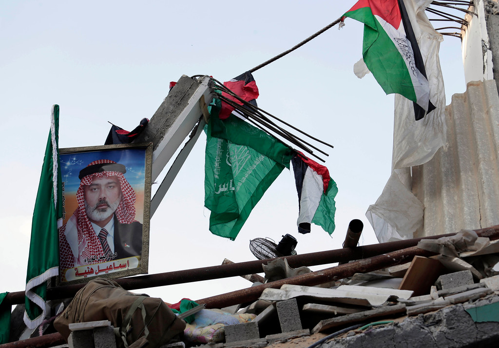 Description of . Palestinian and Islamic flags and a portrait of the top Hamas leader in Gaza, Ismail Haniyeh, are placed on the rubble of his house hit by a pre-dawn Israeli strike, in Gaza City, northern Gaza Strip, Tuesday, July 29, 2014. (AP Photo/Lefteris Pitarakis)