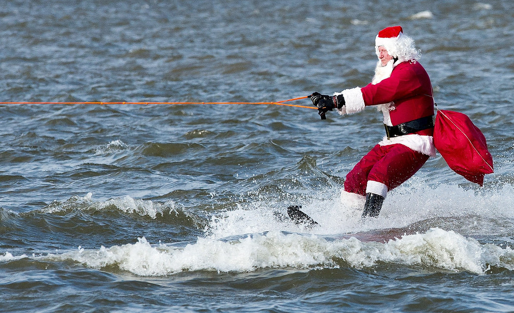 Description of . The water skiing Santa Claus heads down the Potomoc River ON December 24, 2013 at National Harbor, Maryland, near Washington. The group of volunteers are celebrating their 28th anniversary of the event that also has kneeboarding reindeer, flying elves, the jet-sking Grinch, and Frosty the snowman.    AFP PHOTO/Paul J. RichardsPAUL J. RICHARDS/AFP/Getty Images
