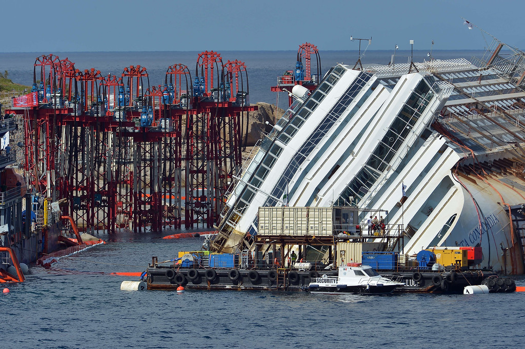 Description of . Members of the US salvage company Titan and Italian firm Micoperi work at the wreck of Italy's Costa Concordia cruise ship near the harbor of Giglio Porto on September 16, 2013. Salvage workers attempt to raise the cruise ship today in the largest and most expensive maritime salvage operation in history, so-called