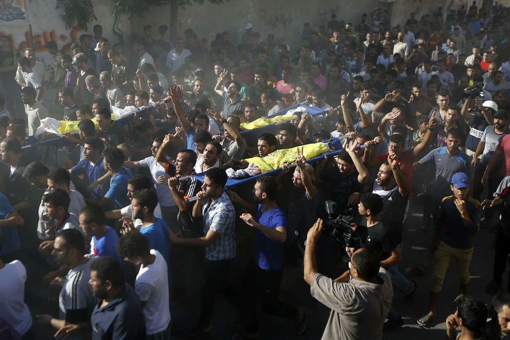Description of . Palestinian mourners shout slogans during the funeral of four boys, all from the Bakr family, in Gaza City, on July 16, 2014. Four children were killed and several injured at a beach in Gaza City medics said, in Israeli shelling witnessed by AFP journalists. The strikes appeared to be the result of shelling by the Israeli navy against an area with small shacks used by fishermen. The deaths raised the overall toll in nine days of violence in Gaza to 213. AFP PHOTO/MOHAMMED ABED/AFP/Getty Images