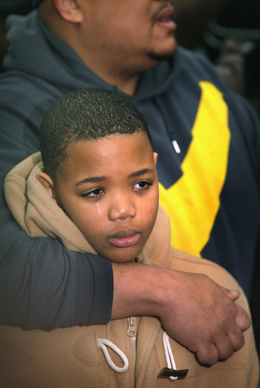 Description of . Nate Pendleton comforts his son Nathaniel, 10, as they listen to speakers at a press conference in a neighborhood park where Nate's daughter Hadiya was killed on January 30, 2013 in Chicago, Illinois. Fifteen-year-old Hadiya was shot and killed when a gunman opened fire in the park yesterday while she was hanging out with friends on the warm rainy afternoon under a shelter in the park. Hadiya was a majorette in her high school band and recently performed in Washington, D.C. during the inauguration. President Obama's Chicago home is less than a mile from the park where Hadiya was killed.   Another person was wounded in the leg during the shooting.   (Photo by Scott Olson/Getty Images)