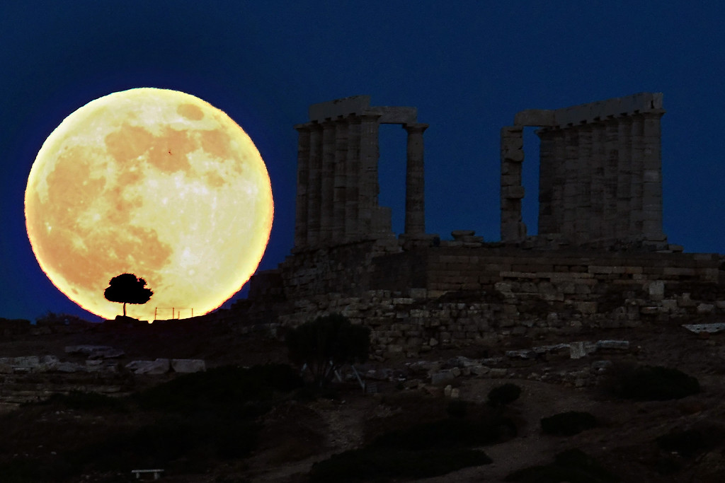 Description of . A supermoon rises next to the ancient Greek temple of Poseidon at Cape Sounion, about 65 kilometers south of Athens, on June 23, 2013.   ARIS MESSINIS/AFP/Getty Images