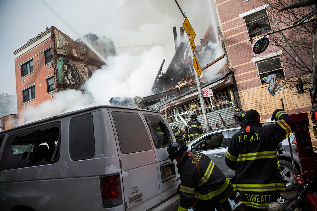 Description of . Firefighters from the Fire Department of New York (FDNY) respond to a 5-alarm fire and building collapse at 1646 Park Ave in the Harlem neighborhood of Manhattan March 12, 2014 in New York City. Reports of an explosion were heard before the collapse of two multiple-dwelling buildings that left at least 11 injured.  (Photo by Andrew Burton/Getty Images)