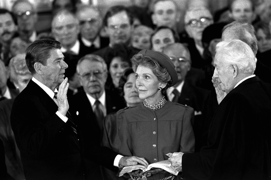 Description of . President Ronald Reagan takes the oath of office in the Rotunda of the Capitol, Monday, January 21, 1985, in Washington as his wife Nancy holds the Bible. Chief Justice Warren Burger gives the President the oath. (AP Photo/BOB DAUGHERTY)