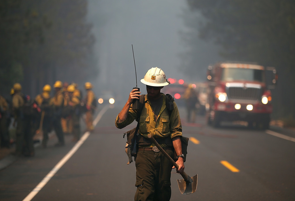 Description of . GROVELAND, CA - AUGUST 22:  A U.S. Forest Service firefighter monitors a radio while battling the Rim Fire on August 22, 2013 in Groveland, California. The Rim Fire continues to burn out of control and threatens 2,500 homes outside of Yosemite National Park. Over 1,000 firefighters are battling the blaze that was reduced to only 2 percent containment after it nearly tripled in size overnight.  (Photo by Justin Sullivan/Getty Images)