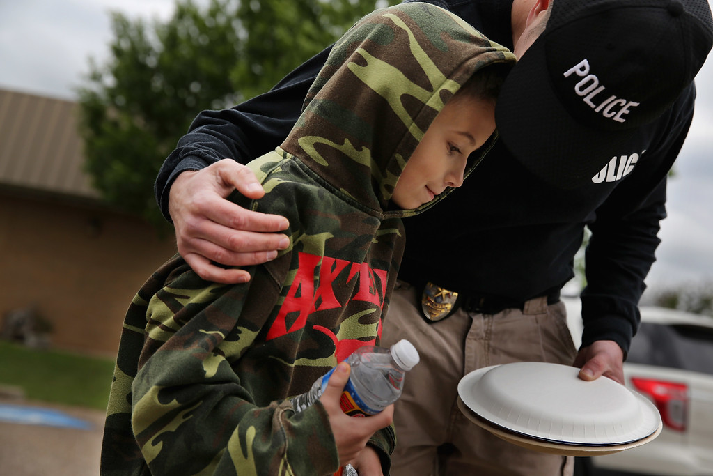 Description of . WEST, TX - APRIL 18:  Hewitt, Texas police officer Mike Zahirniak (R) comforts his son, Coy Zahirniak, 9, outside the West Community Center the day after the West Fertilizer Company explosion April 18, 2013 in West, Texas. Coy alerted his family to the fire across the street from his grandfather Willie Zahirniak's home and the plant exploded as they evacuated. The home was destroyed and Coy has been credited for saving his family from harm. The fertilizer company caught fire and exploded, killing more than five people, injuring more than 160 people and leaving damaged buildings for blocks in every direction.  (Photo by Chip Somodevilla/Getty Images)