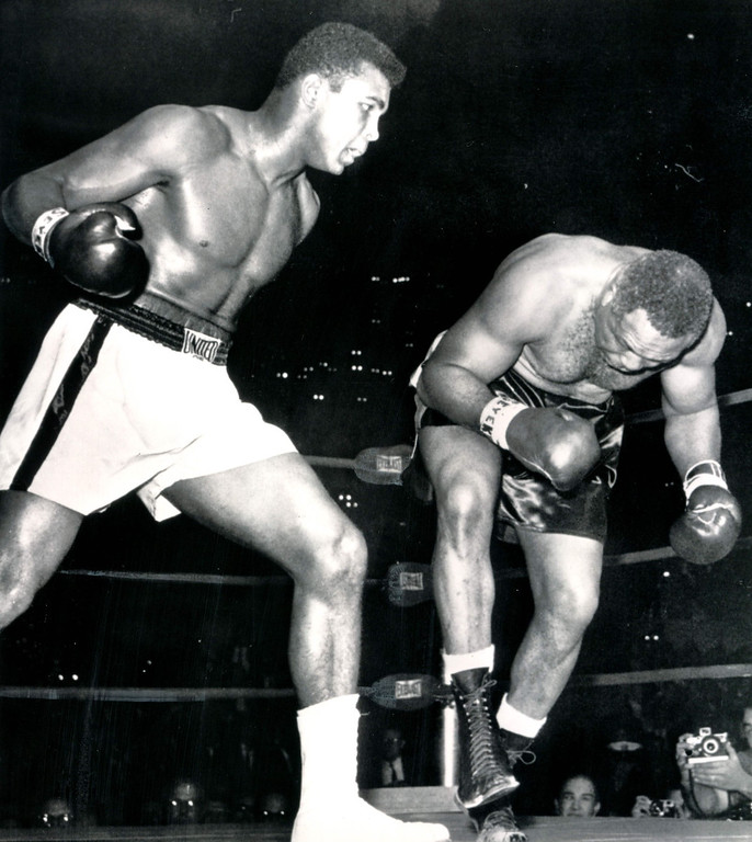 Description of . LOS ANGELES, Nov.15, 1962--HEADED FOR THE CANVAS--Toppled by a barrage of lefts and rights, Archie Moore starts his second trip to the canvas in the fourth round of his scheduled 12-rounder against Cassius Clay in Los Angeles tonight.  When he went down for the third time referee Tommy Hart stopped the fight at one minute and 35 seconds. Credit: AP